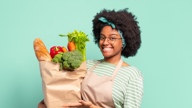 Young pretty afro woman smiling cheerfully, pointing to the side and upwards holding a vegetables bag