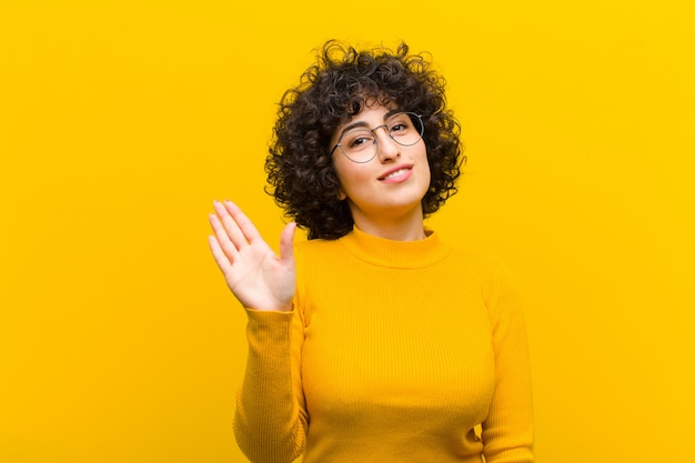 Young pretty afro woman smiling happily and cheerfully, waving hand, welcoming and greeting you, or saying goodbye