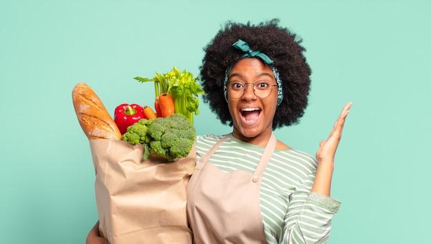 フレンドリーで自信に満ちた、前向きな表情で幸せそうに笑って、オブジェクトやコンセプトを提供して見せ、野菜のバッグを持っている若いかなりアフロの女性