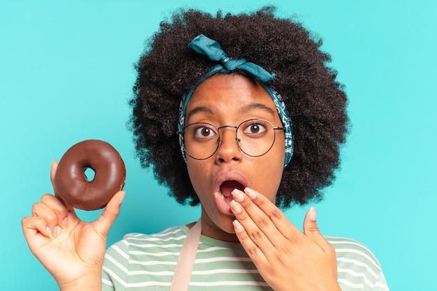 ドーナツを持つ若いかなりアフロの女性