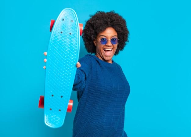 スケート ボードを持つ若いかわいいアフロ女性