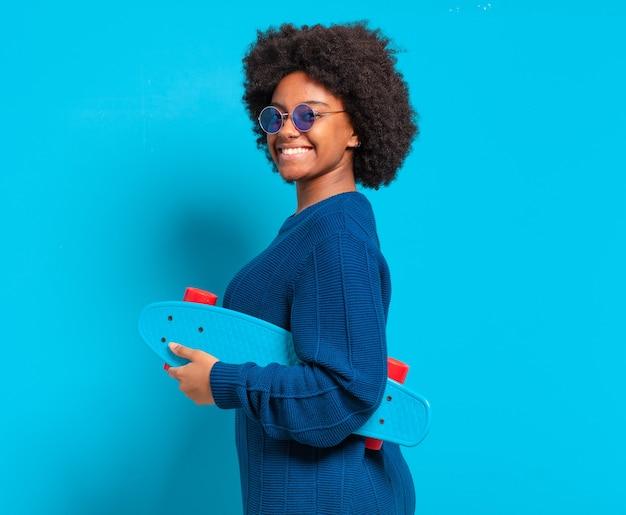 スケートボードを持つ若いかなりアフロの女性
