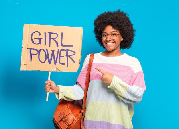 Young pretty afro woman with girl power board
