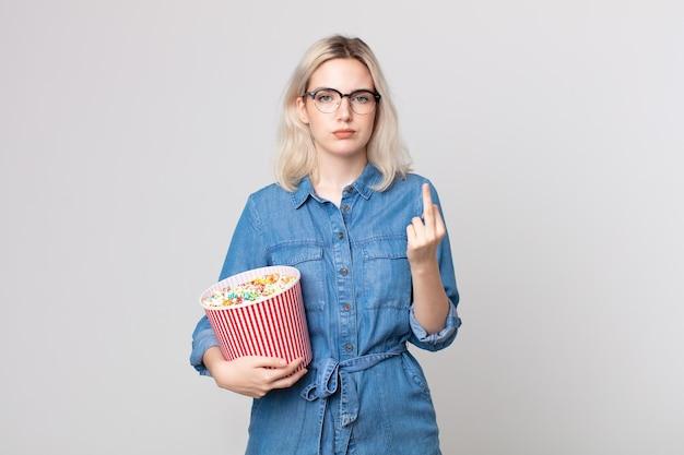 팝콘 양동이를 들고 화나고, 짜증나고, 반항적이고, 공격적인 젊은 알비노 여성