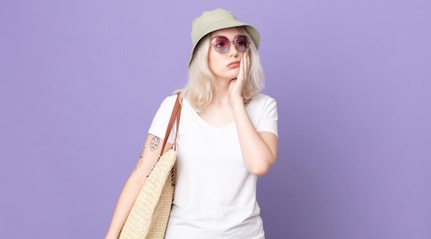 Молодая красивая женщина-альбинос чувствует себя скучающей, расстроенной и сонной после утомительного. летняя концепция