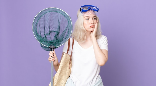 Young pretty albino woman feeling bored, frustrated and sleepy after a tiresome with goggles and a fishing net