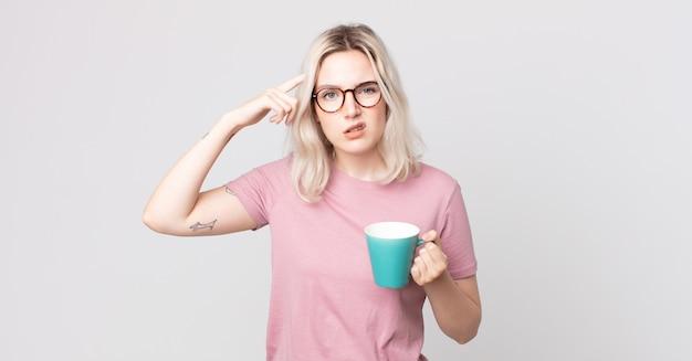 混乱して困惑している若いかなりアルビノの女性は、あなたがコーヒーマグで狂っていることを示しています