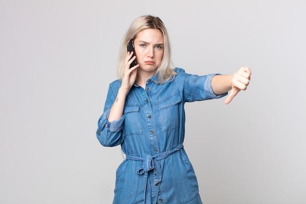 Молодая красивая женщина-альбинос чувствует себя раздраженной, показывает палец вниз и разговаривает со смартфоном