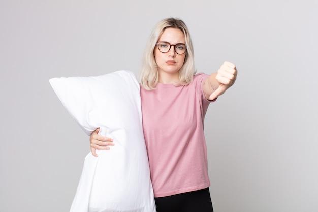Молодая симпатичная женщина-альбинос чувствует злость, показывает палец вниз в пижаме и держит подушку