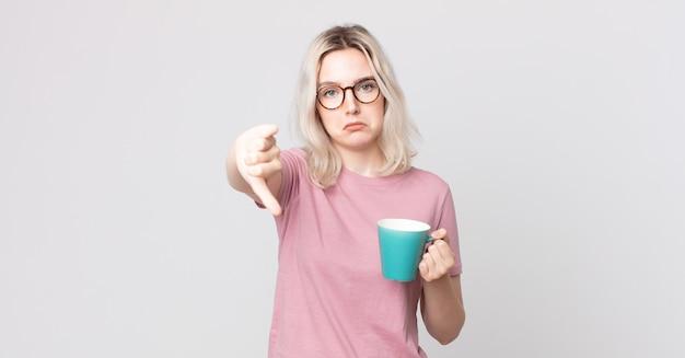 Young pretty albino woman feeling cross,showing thumbs down with a coffee mug