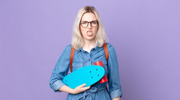 うんざりしてイライラし、舌を出してスケートボードを持っている若いかなりアルビノの女性