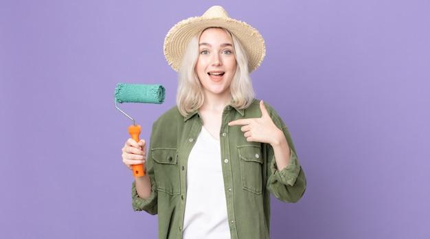 Молодая красивая женщина-альбинос чувствует себя счастливой и показывает на себя возбужденным и держит валик с краской
