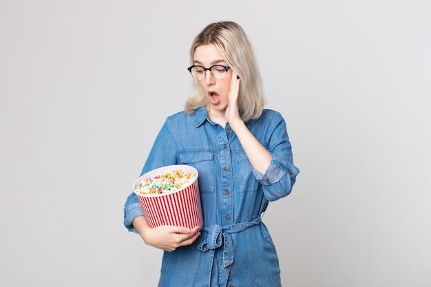 Молодая красивая женщина-альбинос чувствует себя счастливой, взволнованной и удивленной с ведром поп-кукурузы