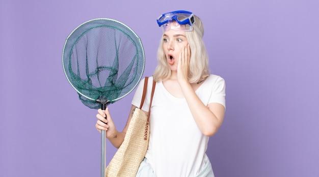 ゴーグルと漁網で幸せ、興奮、驚きを感じている若いかわいいアルビノの女性