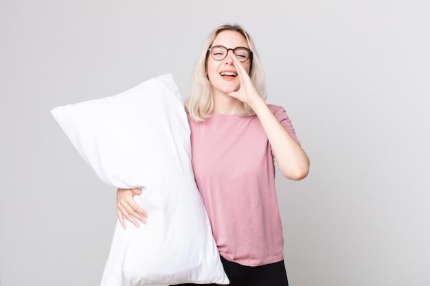 Молодая красивая женщина-альбинос чувствует себя счастливой, громко кричит, держа руки у рта в пижаме и держа подушку