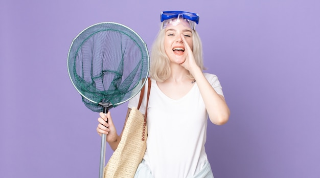 Молодая красивая женщина-альбинос чувствует себя счастливой, громко кричит, прижав руки ко рту в очках и с рыболовной сетью