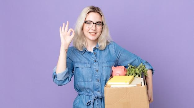 Молодая красивая женщина-альбинос чувствует себя счастливой, показывая одобрение жестом в порядке. концепция увольнения