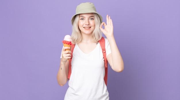 Молодая красивая женщина-альбинос чувствует себя счастливой, показывая одобрение с нормальным жестом. летняя концепция