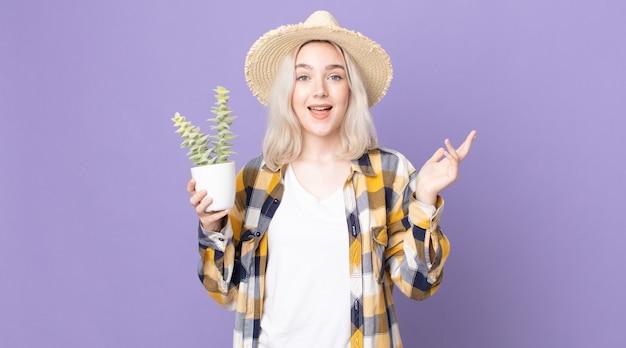 幸せを感じ、解決策やアイデアを実現し、観葉植物のサボテンを持って驚いた若いかなりアルビノの女性