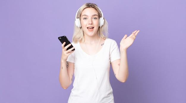 幸せを感じ、ヘッドフォンとスマートフォンで解決策やアイデアを実現して驚いた若いかなりアルビノの女性