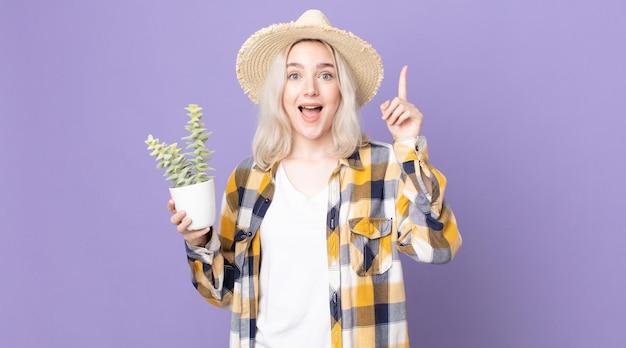 アイデアを実現し、観葉植物のサボテンを持った後、幸せで興奮した天才のように感じている若いかわいいアルビノの女性