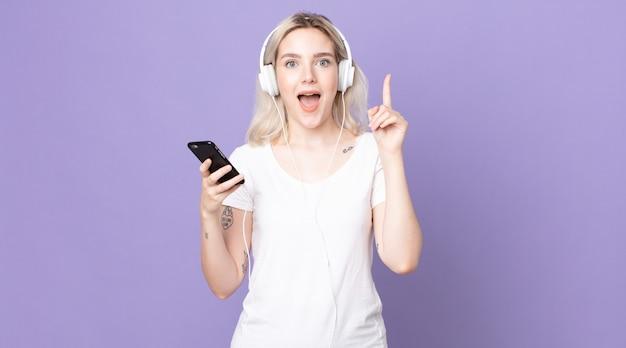 ヘッドフォンとスマートフォンでアイデアを実現した後、幸せで興奮した天才のように感じる若いかわいいアルビノの女性