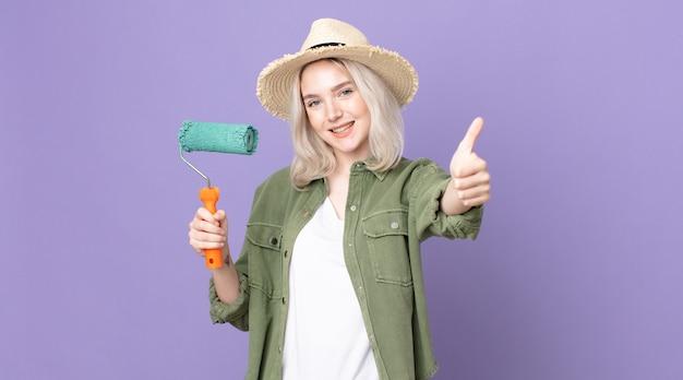 Молодая красивая женщина-альбинос чувствует гордость, позитивно улыбается, показывает палец вверх и держит валик с краской