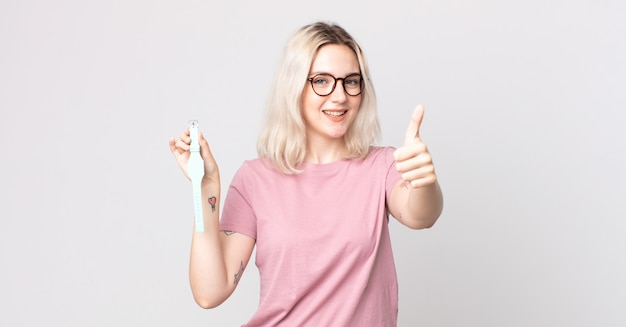 Молодая красивая женщина-альбинос чувствует гордость, позитивно улыбается, показывает палец вверх и держит наручные часы