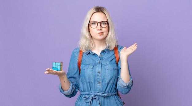 어리고 예쁜 알비노 여성은 어리둥절하고 혼란스러워하며 지능 게임을 의심하고 해결합니다