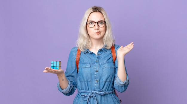 Young pretty albino woman feeling puzzled and confused and doubting and solving an intelligence game