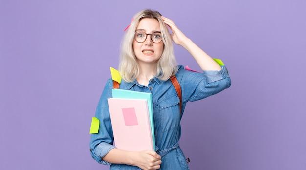 젊고 예쁜 알비노 여성은 머리에 손을 얹고 스트레스를 받거나 불안해하거나 무서워합니다. 학생 개념