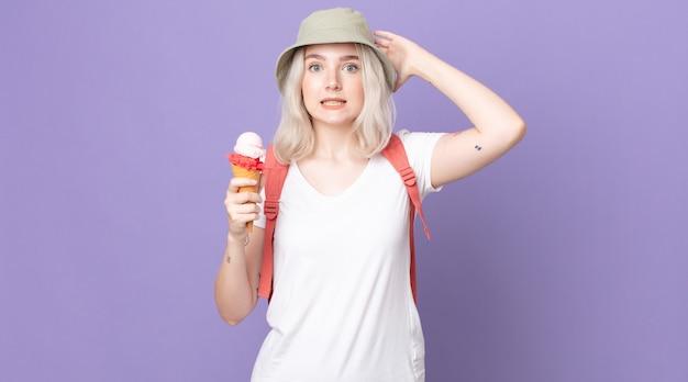 Молодая красивая женщина-альбинос чувствует себя подчеркнутой, встревоженной или испуганной, с руками на голове. летняя концепция