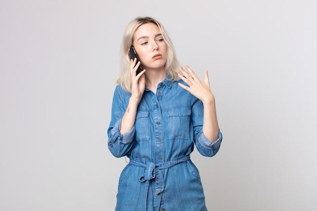 Молодая красивая женщина-альбинос чувствует стресс, тревогу, усталость и разочарование и разговаривает со смартфоном