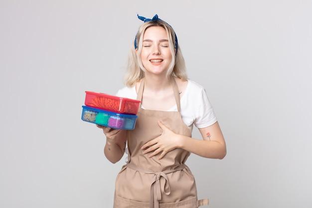 食品タッパーウェアを保持しているいくつかの陽気な冗談で大声で笑っている若いかわいいアルビノの女性