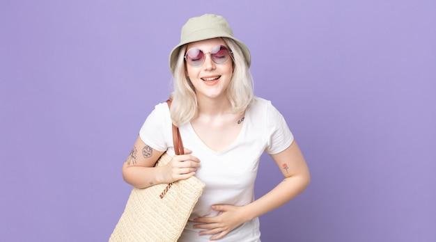 Молодая красивая женщина-альбинос громко смеется над какой-то веселой шуткой. летняя концепция