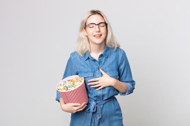 ポップコーンのバケツでいくつかの陽気な冗談で大声で笑っている若いかわいいアルビノの女性