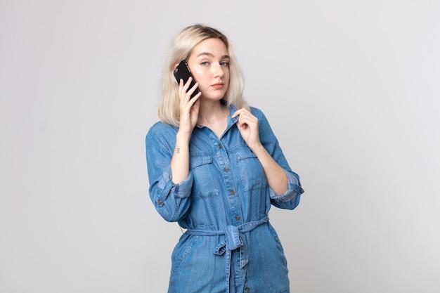 Молодая симпатичная женщина-альбинос выглядит высокомерной, успешной, позитивной и гордой и разговаривает со смартфоном
