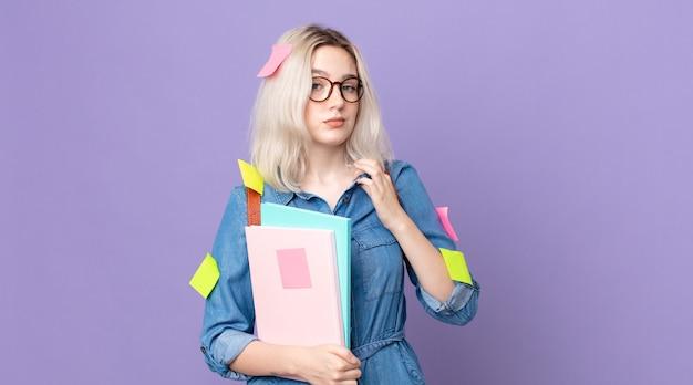 Молодая красивая женщина-альбинос выглядит высокомерной, успешной, позитивной и гордой. студенческая концепция