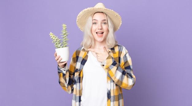 興奮して驚いた若いかわいいアルビノの女性が横を指して観葉植物のサボテンを持っています