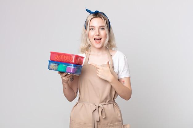 食品タッパーウェアを保持している側を指して興奮して驚いて見える若いかわいいアルビノの女性