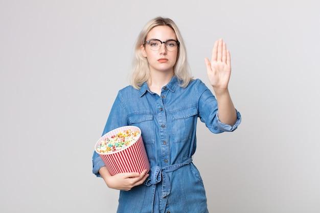 Молодая симпатичная женщина-альбинос выглядит серьезной, показывая открытую ладонь, делая жест с ведром для кукурузы