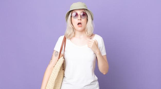 Молодая красивая женщина-альбинос выглядит шокированной и удивленной с широко открытым ртом, указывая на себя. летняя концепция