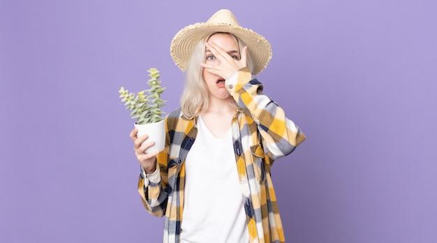 Молодая симпатичная женщина-альбинос выглядит потрясенной, напуганной или напуганной, закрывая лицо рукой и держа кактус комнатное растение