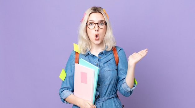 Молодая красивая женщина-альбинос выглядит удивленной и шокированной, с отвисшей челюстью, держащей предмет. студенческая концепция