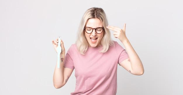 Молодая красивая женщина-альбинос выглядит несчастной и подчеркнутой, жест самоубийства делает знак пистолета и держит часы с часами