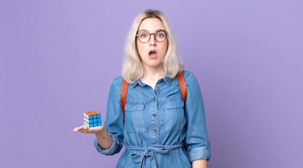 Молодая красивая женщина-альбинос выглядит очень шокированной или удивленной и решает интеллектуальную игру