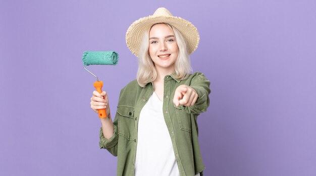 Молодая красивая женщина-альбинос, указывая на камеру, выбирает вас и держит валик с краской