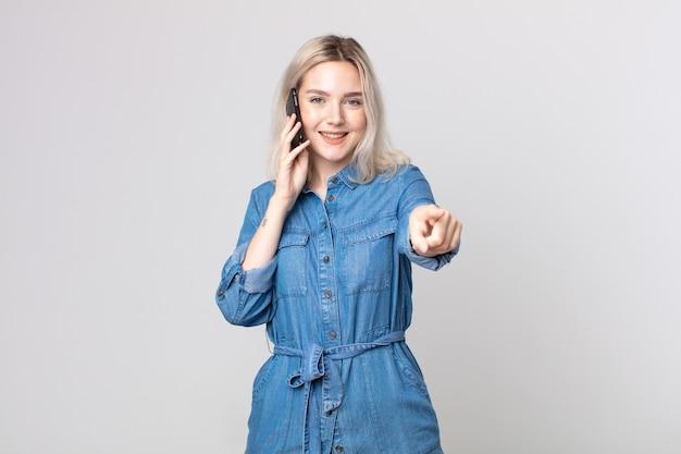 Молодая красивая женщина-альбинос, указывая на камеру, выбирает вас и разговаривает со смартфоном