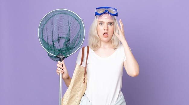 Молодая красивая женщина-альбинос кричит с поднятыми руками в очках и с рыболовной сетью
