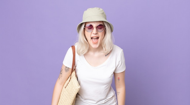 Молодая красивая женщина-альбинос агрессивно кричит, выглядит очень сердитой. летняя концепция